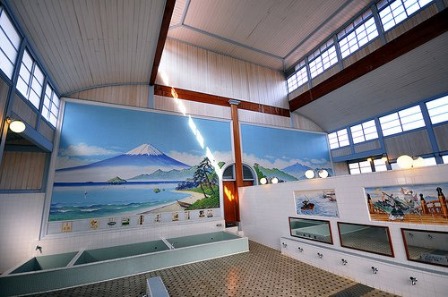 A traditional (non-super) Tokyo sento. Bathers wash at the taps in front of the mirrors, before entering the tubs at the back of the room. The wall on the right divides the men's and women's sides